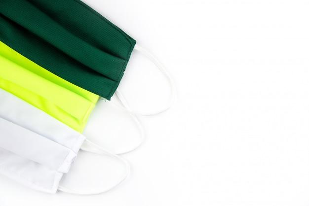 Maschera di cotone verde chiaro e bianca verde o maschera del tessuto su fondo bianco. polvere e virus protettivi. maschera preventiva in cotone coronavirus.