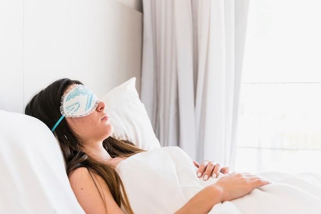 Maschera di occhio d'uso della giovane donna che dorme sul letto nella camera da letto