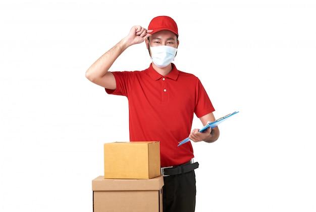 Maschera di protezione d'uso del fattorino asiatico in uniforme rossa che sta con il contenitore di posta del pacchetto isolato sopra fondo bianco. servizio di corriere espresso durante covid19.