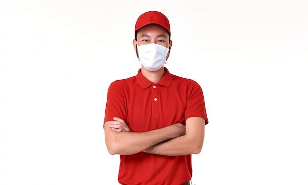 Maschera di protezione d'uso del fattorino asiatico in uniforme rossa isolata sopra fondo bianco.