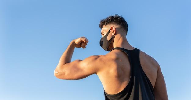Maschera di protezione d'uso dell'uomo caucasico atletico che mostra il suo bicipite sul fondo del cielo blu. concetto di lotta contro il coronavirus covid-19. copia spazio