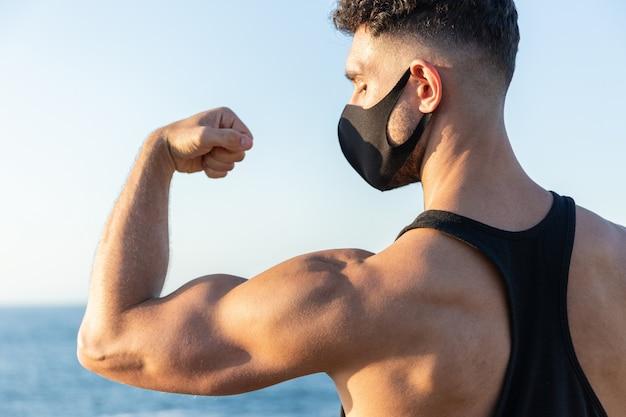 Maschera di protezione d'uso dell'uomo caucasico atletico che mostra il suo bicipite sul fondo del cielo blu. concetto di lotta contro il coronavirus covid-19
