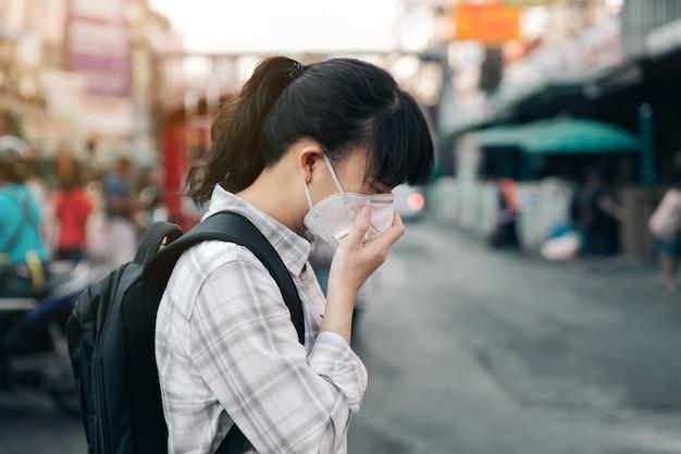 Maschera di protezione d'uso della donna asiatica che tossisce a causa di inquinamento atmosferico nella città