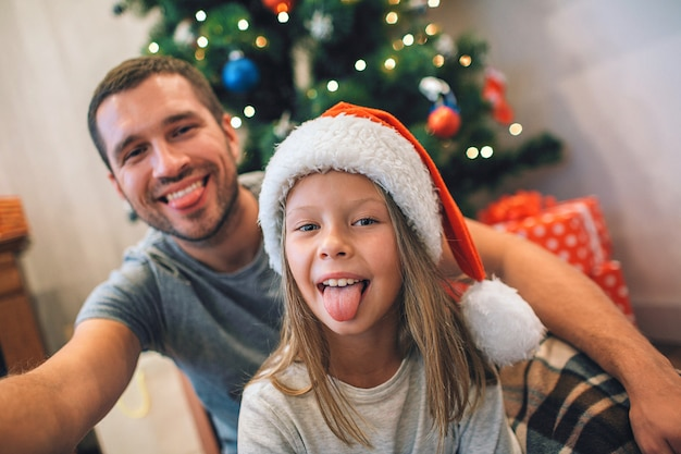 Maschera divertente del padre e della figlia che mostrano le lingue