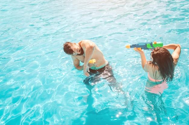 Maschera divertente delle coppie che giocano nella piscina. la ragazza sta sparando nel ragazzo dalla pistola ad acqua. cerca di difendersi. si divertono molto.