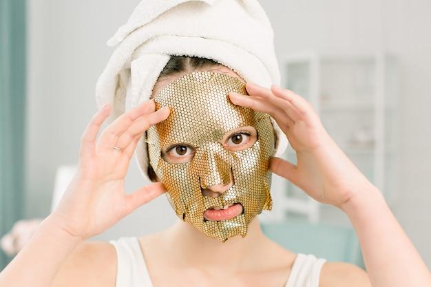 Maschera donna foglio d'oro. bellissima giovane donna spugna bianca sulla testa con golden skin cosmetic, guardando la fotocamera. beauty skincare and treatment