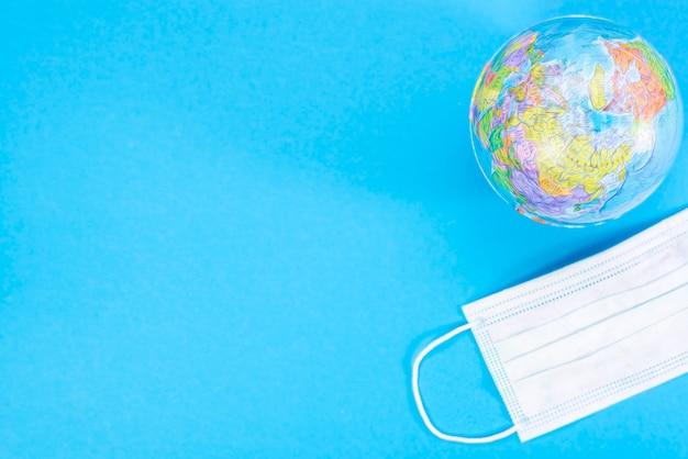 Maschera e globo medici a gettare, concetto di pandemia. kovid-19, coronavirus. l'epidemia globale della malattia