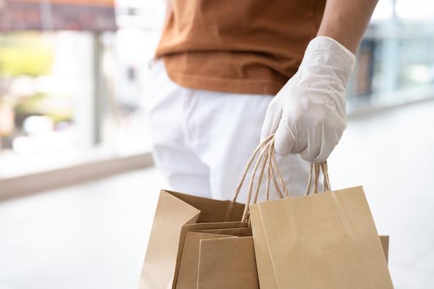 Maschera e guanti di usura del fattorino che tengono la borsa dell'alimento per servizio di sicurezza