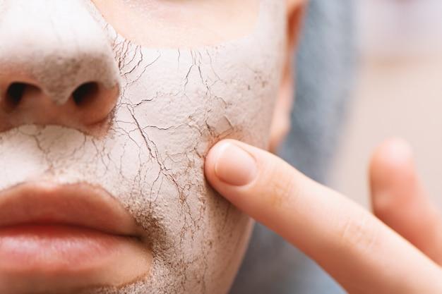 Maschera facciale dell'argilla sul fronte femminile, fine in su.