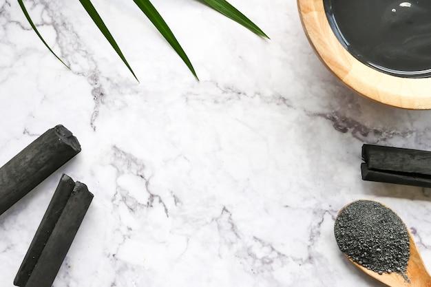 Maschera facciale e scrub con carbone attivo in polvere sul tavolo di marmo