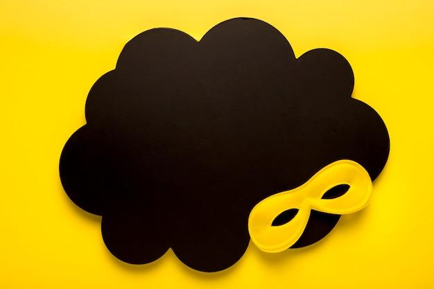 Maschera gialla di carnevale sulla nuvola di carta nera