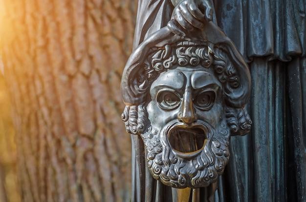 Maschera lacrimosa di una scultura in rame in un parco forestale