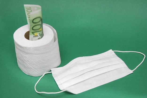 Maschera medica accanto a un rotolo di carta igienica e una fattura da 100 euro.