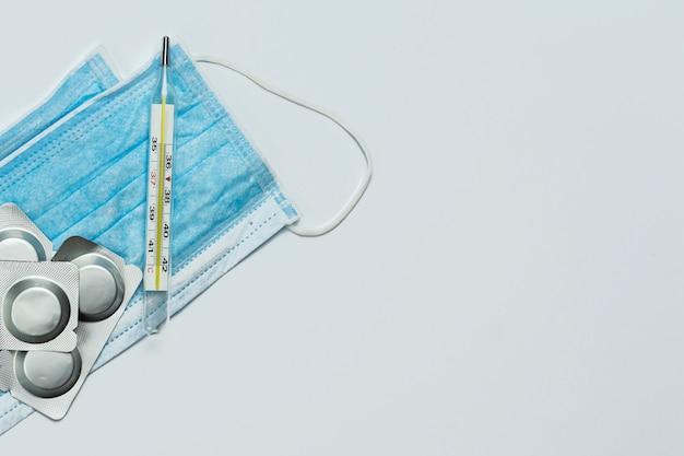 Maschera medica blu vicino al termometro e alle pillole