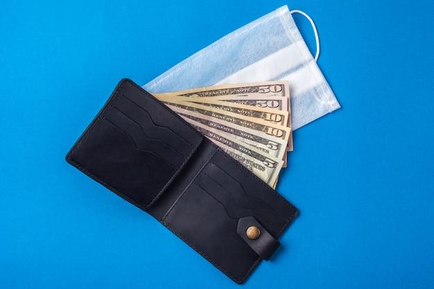 Maschera medica e denaro. visiera medica su soldi americani. concetto di crisi finanziaria