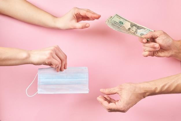 Maschera medica e dollari in mano come concetto di aumento dei prezzi per la protezione dai virus.