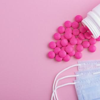 Maschera medica protettiva chirurgica virus, influenza, malattia e pillole. isolato su uno sfondo rosa.
