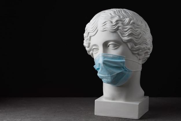 Maschera medica su una statua antica. assistenza medica epidemica virale