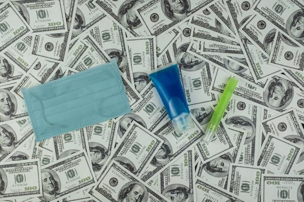 Maschera medico e protezione da virus bottiglia di gel per alcool e denaro una pila di banconote da 100 dollari statunitensi molto