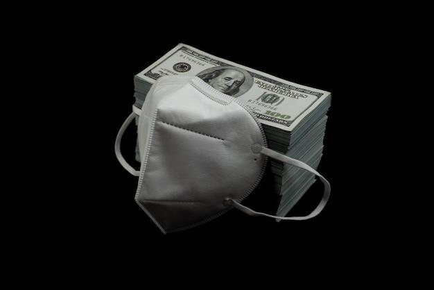 Maschera medico protezione antivirus e denaro una pila di banconote da 100 dollari americani molto sulla superficie nera, che costava un prezzo costoso e un concetto di prodotti ad alto prezzo