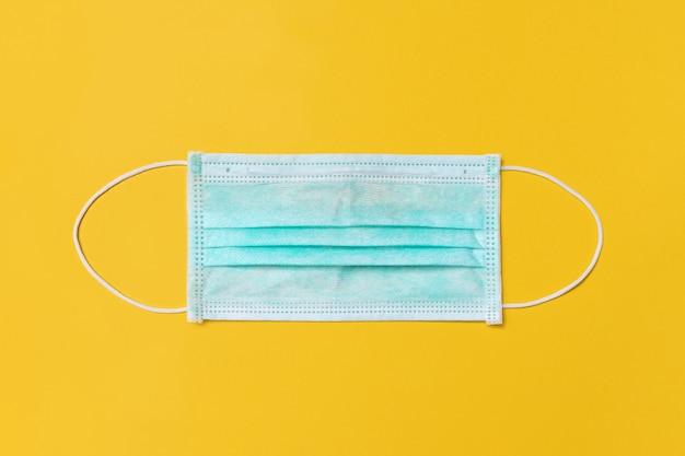 Maschera monouso medica su sfondo giallo, protezione e prevenzione per diffusione covid-19 o wuhan novel coronavirus