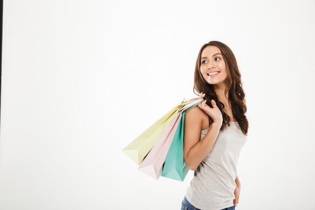 Maschera orizzontale della donna d'avanguardia che posa sulla macchina fotografica con i pacchetti di acquisto a disposizione, isolata sopra lo spazio bianco della copia della parete