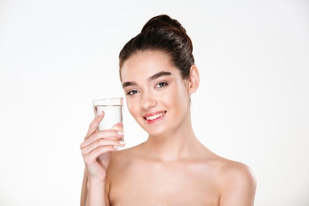 Maschera orizzontale della donna felice e in buona salute che è mezza nuda che beve acqua minarale da vetro trasparente con il sorriso