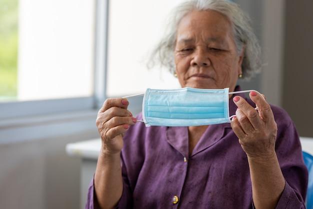 Maschera per il viso d'uso della donna asiatica senior durante il virus della corona e l'epidemia di influenza. protezione da malattie e malattie. la paziente anziana che è a rischio di infezione da virus corona [covid-19].