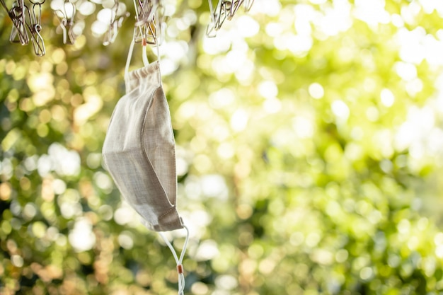Maschera per il viso in cotone biologico appesa su stendibiancheria. maschera lavabile in tessuto dopo il lavaggio per il riutilizzo
