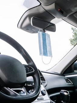 Maschera protettiva appesa allo specchietto retrovisore di un'auto.