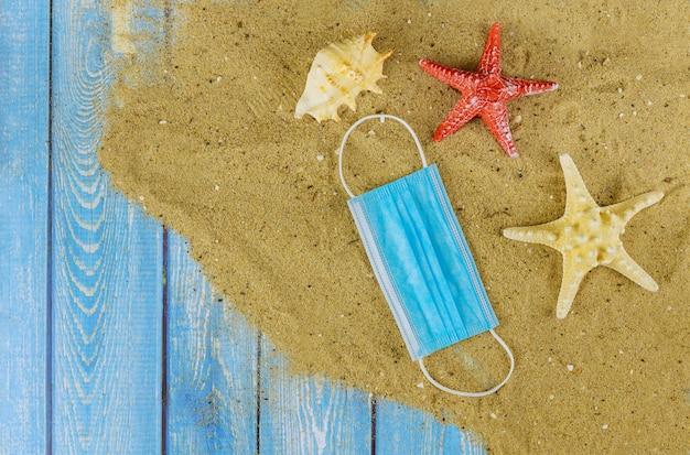 Maschera protettiva medica su una spiaggia di sabbia al momento della pandemia di coronavirus.