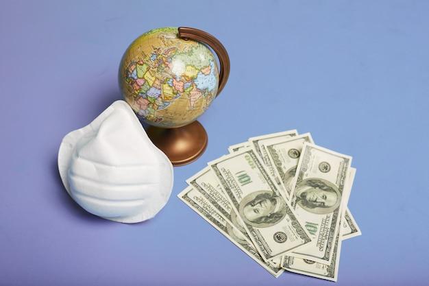 Maschera protettiva medica, un piccolo globo e banconote in dollari come simbolo di una pandemia mondiale, un'epidemia di covid-19 e crisi finanziaria, isolata a sfondo blu. copia spazio per il testo