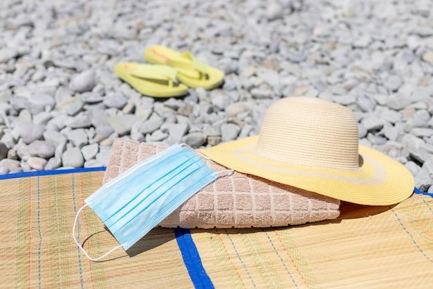 Maschera protettiva, telo mare, cappello di paglia e infradito sulla spiaggia