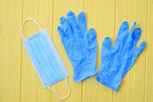 Maschera respiratoria e guanti blu sulla parete gialla. chiama per la disinfezione delle mani. interrompere il concetto di coronavirus