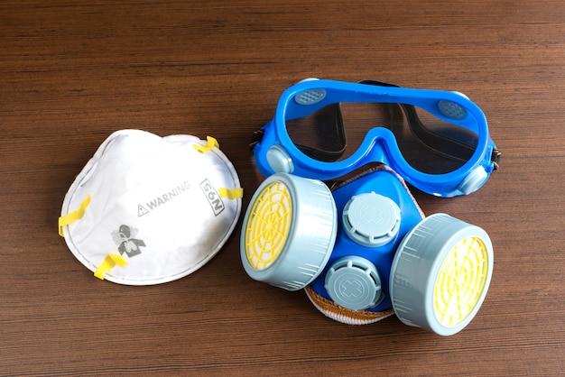 Maschera respiratoria, maschera antipolvere e maschera di sicurezza per prodotti chimici industriali su fondo di legno.