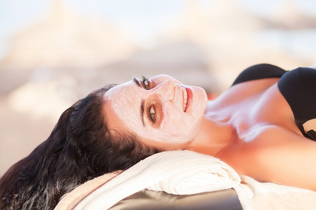 Maschera spa. la bella donna ottiene la maschera della stazione termale sulla spiaggia soleggiata nel salone della stazione termale all'aperto. alta qualità. cura della cicatrice.
