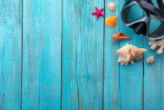 Maschera subacquea con le stelle marine e le conchiglie su vecchio di legno blu. vista dall'alto. disteso.