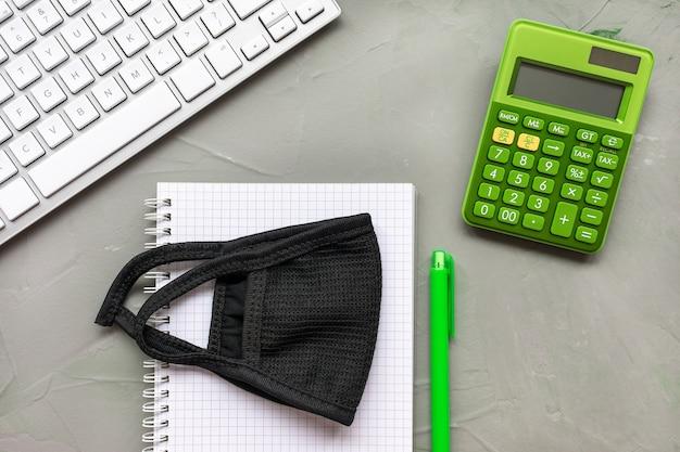 Maschera, tastiera, calcolatrice e taccuino su grigio, piatto laici