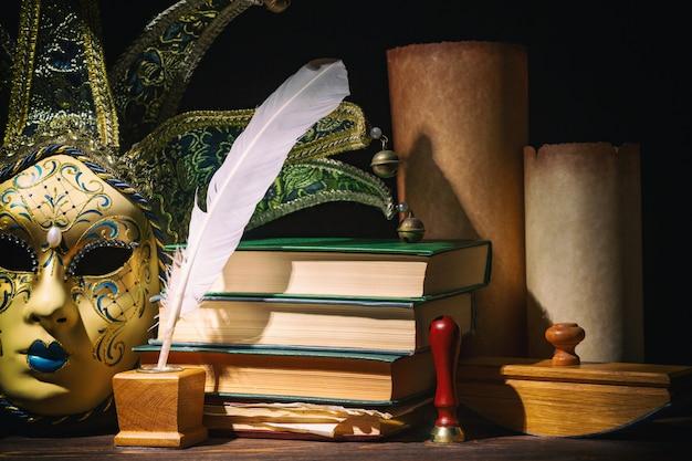 Maschera veneziana con vecchio calamaio, piuma, penna, pergamene, libri e sigillo sul tavolo di legno.