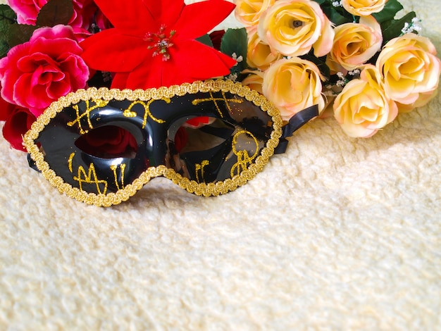 Maschera veneziana nera a fantasia dorata con fiori.