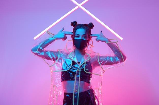 Maschera virus donna asiatica che indossa una protezione per il viso intorno al neon colorato