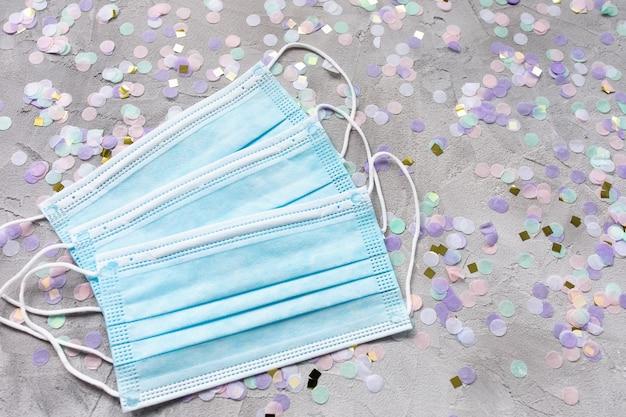Maschere chirurgiche blu per la bocca e coriandoli colorati a terra.
