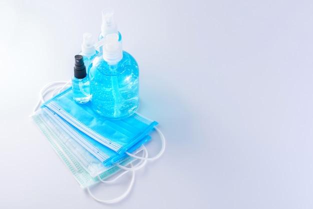 Maschere chirurgiche e gel disinfettante per mani per alcol per la protezione della diffusione dell'igiene prevenzione dei germi coronavirus (covid-19) su sfondo bianco con spazio di copia