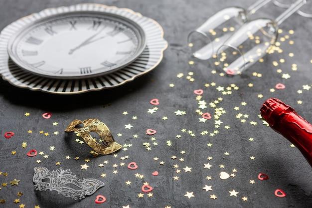 Maschere di carnevale, bottiglie di champagne e due bicchieri di champagne e coriandoli glitter oro, vista dall'alto, close up su sfondo grigio,