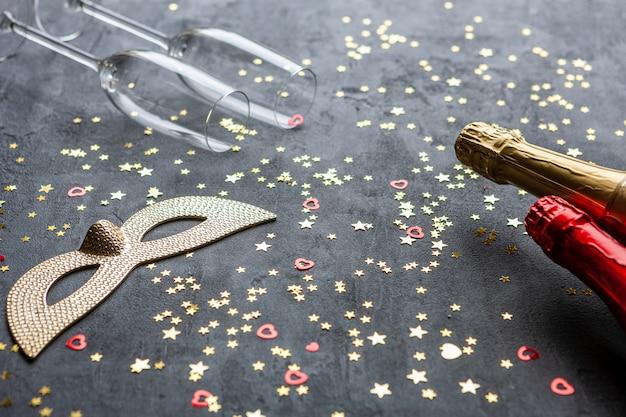 Maschere di carnevale, bottiglie di champagne e due bicchieri di champagne e coriandoli glitter oro,