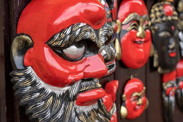 Maschere di legno tradizionali che appendono per la vendita sul mercato di strada a hanoi, vietnam, primo piano