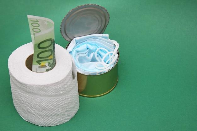 Maschere mediche in una lattina accanto a un rotolo di carta igienica e una fattura da 100 euro.