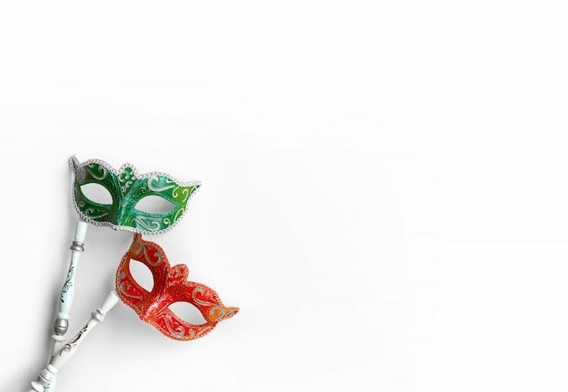 Maschere veneziane di carnevale in verde e rosso con manico su sfondo bianco