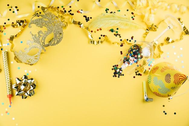 Mascherina della piuma di carnevale con il materiale della decorazione del partito e cappello del partito su fondo giallo
