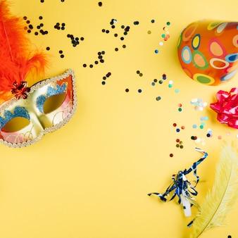 Mascherina della piuma di carnevale di travestimento con il materiale della decorazione del partito ed il cappello del partito sopra fondo giallo
